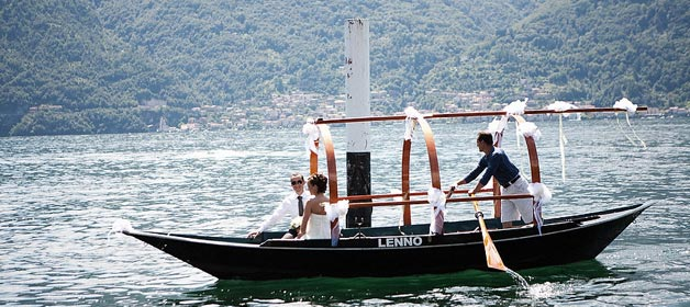 """Getting married at Lake Como, bride and groom arrive by traditional row-boat """"Lucia"""""""