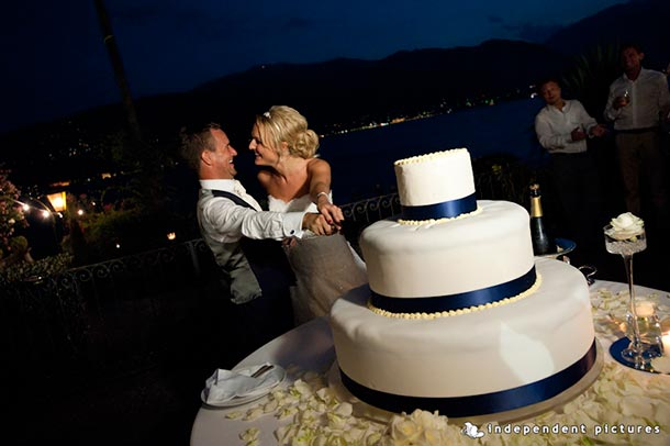 Caroline and Tony's wedding - July 2012 Cutting of the big wedding cake! A blue themed wedding for Caroline and Tony. At night with the lake as backdrop - photo by Independent Pictures.